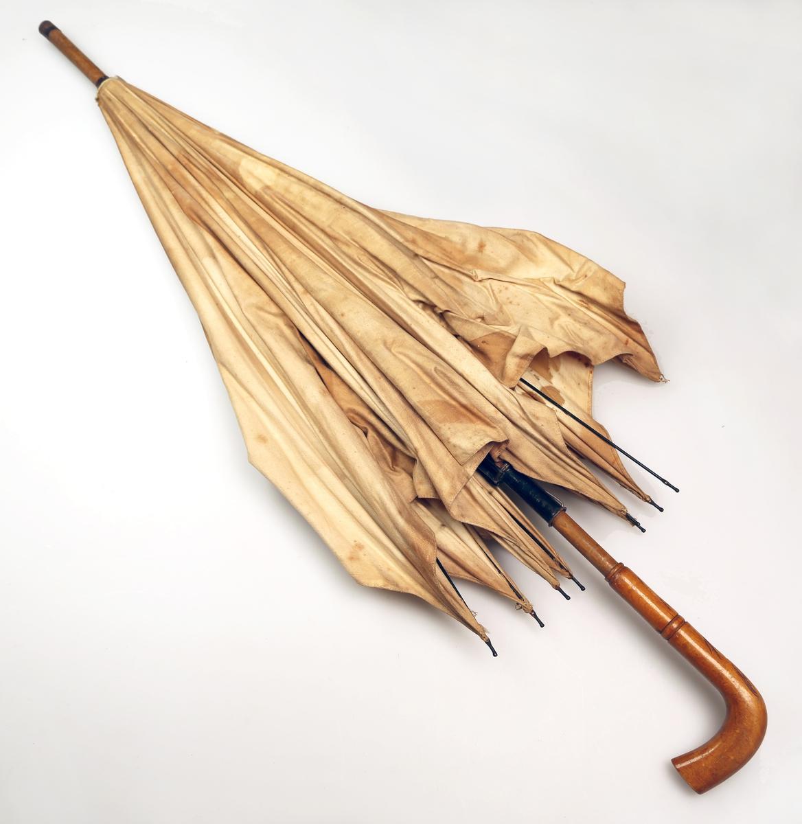 Praply med håndtak og stang av tre, som er lakkert, og spiler av metall, samt trekk av kypertvevd stoff (trolig bomull). I enden er det et metallbeslag. Håndtaket har enkel skåret strekdekor