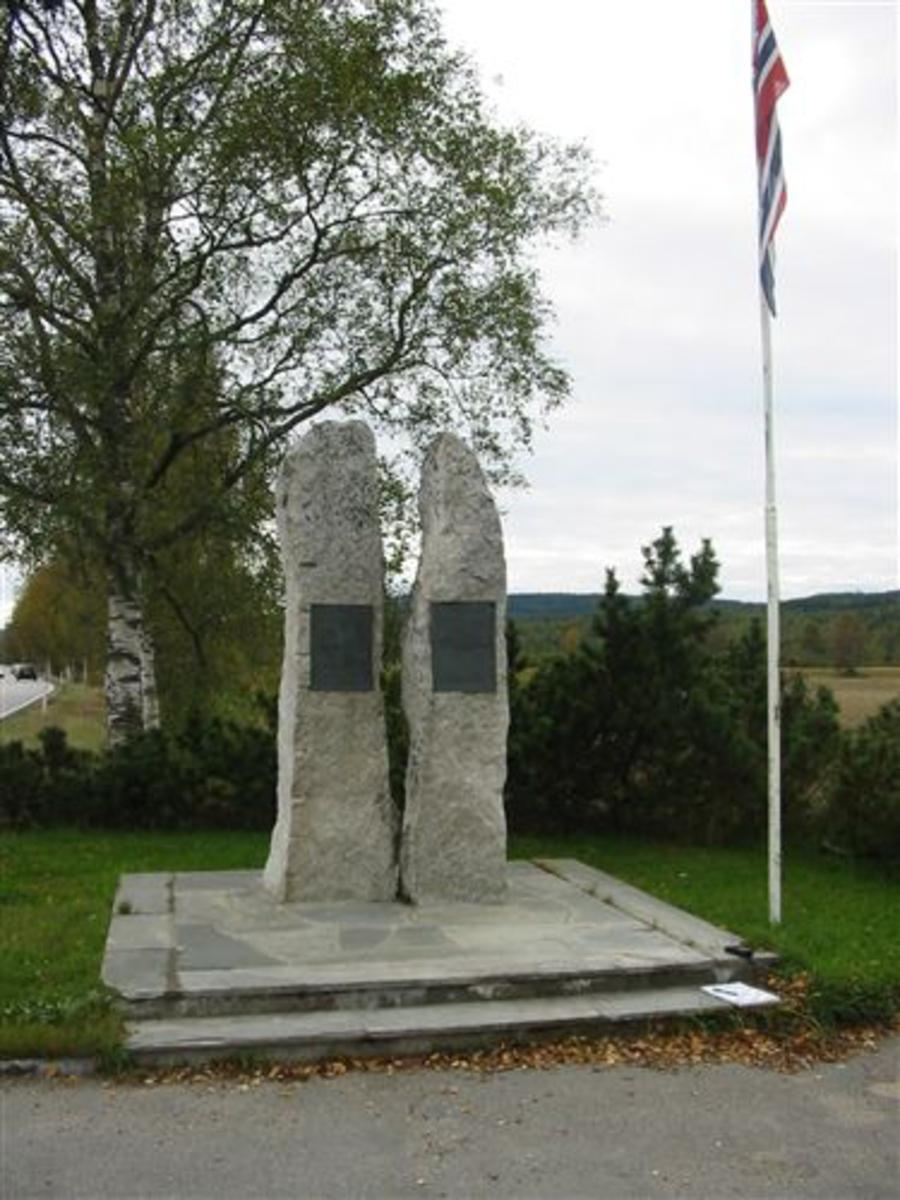 To steinblokker i gneis, ca. 2,5 m høye. Høyre stein har inskripsjon (innfelt plate) om hvorfor bautaen er reist. Venstre stein har inskripsjon (innfelt plate) over de falne.