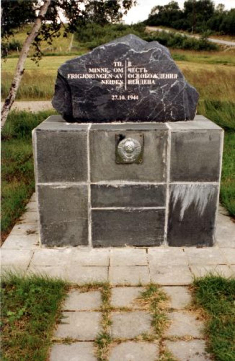 Naturstein funnet i Sør-Varanger med innhuggen tekst Steinen står på en mursokkel belagt med skiferstein. På sokkelen er påmontert det sov riksvåpen