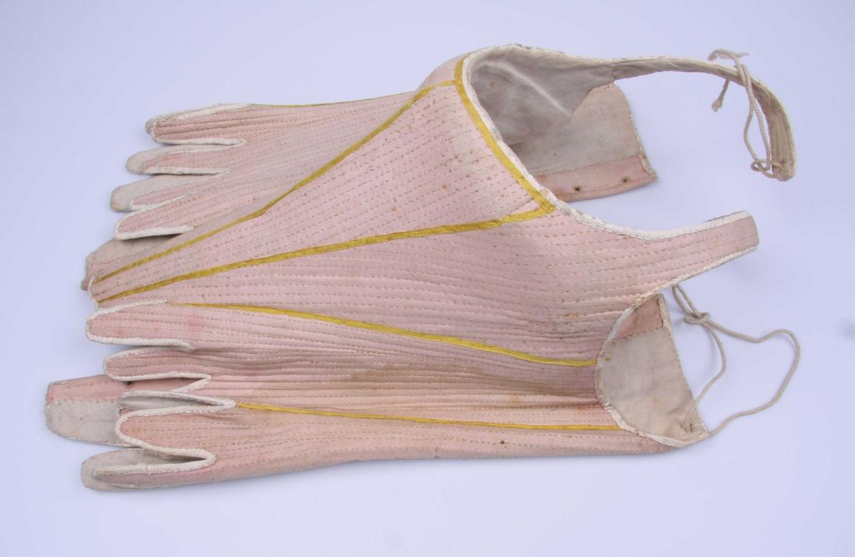 Av rosa linlerret med hvitt linnlerretsfôr, tett besatt med spiler av fiskeben, avstivet og en del vattert ved brystet og nedover magen. Utringingen er dyp og vid, med seler over skuldrene som knyttes til bakstykkene. Korsettet er utskrådd i sidene nederst og har snøring i ryggen. Nedentil er det splittet opp i lange, smale tunger med en bredere, rett avskåret tunge midt foran og midt bak. Spilene går helt ned i tungene. Oventil, langs ermhullene og nedentil er korsettet kantet med hvitt skinn og utvendig påsydd vertikalt, gule smale silkebånd med jevne mellomrom. Fôret er skåret til etter korsettets hoveddeler.