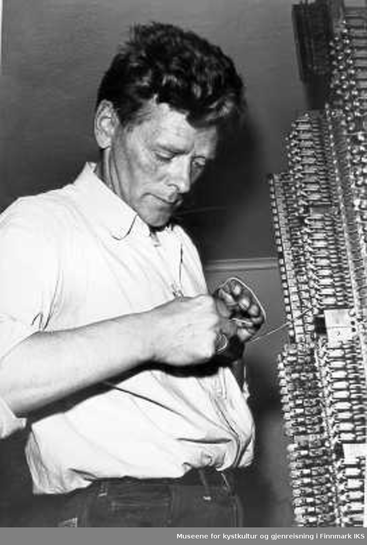 Birger Johansen, montør i Televerket, sjekker sikringer - kobling/sikringstativ i gamle telebygget,  1960