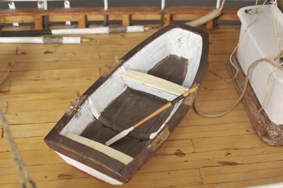 Modell av redningsskjøyte, type Colin Archer.  Form som de første redningsskjøytene. Seilbåt Formaster: 1 stk: h = 102 cm Bakmaster: 1 stk: h = 60 cm  Seilføring: 1 fokke, 1 storseil, 1 mesanseil  Styrhus bak 1 lettbåt med årer