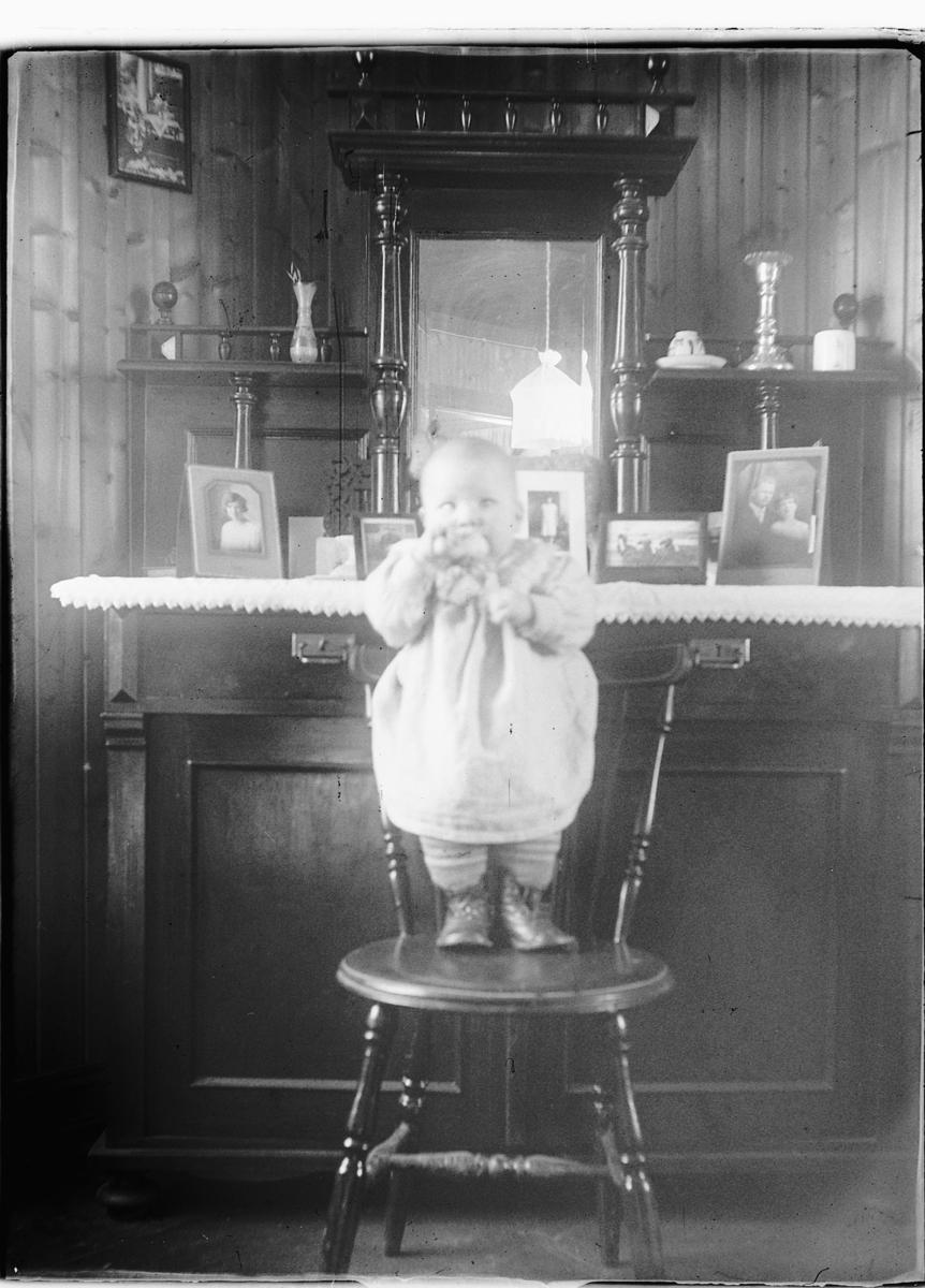 Lite barn står på en stol i en stue.