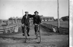 To menn med armene rundt hverandre, på hver sin sykkel, på e