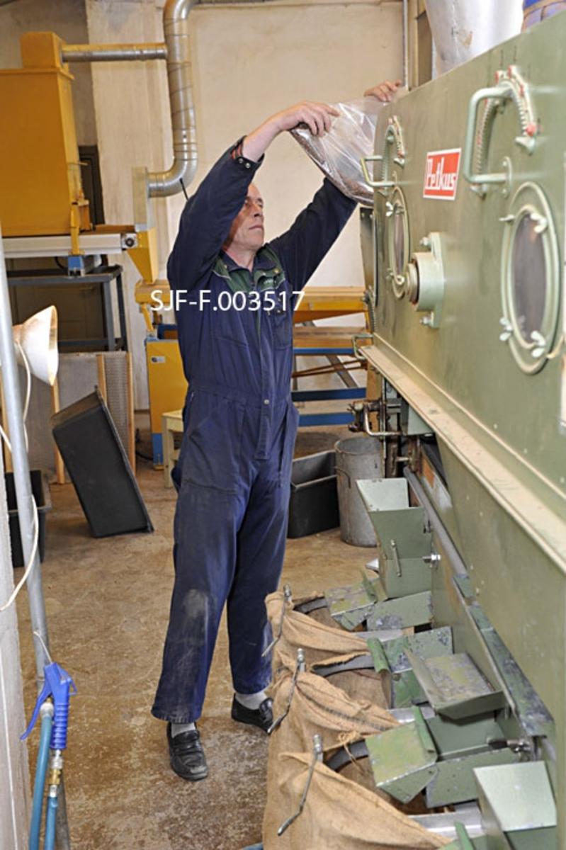 """Frode Murud tømmer et frøparti opp i inntaksskuffen på den tyskproduserte Petkus-maskinen Skogfrøverket bruker til å rense avvinget frø, før det tappes på lufttette kanner og legges på fryselager.  Inntaksskuffen sitter i den bakre tverrenden av maskinen, omtrent i hodehøyde.  Derfra drysses det – stimulert av rystelser i maskinen – ned på et underliggende finmasket nett, hvor de minste ureinhetene faller ned i en metalldunk med et kvadratisk, traktformet toppstykke.  Denne dunken står rett og slett på golvet.  Fra det finmaskete nettet under frøbeholderen triller frøet ned på ei svakt skråstilt såldplate med perforerte hull.  Denne plata er utskiftbar.  Ved rensing av granfrø brukes vanligvis plater der hullene har en diameter på 3, 0 eller 3, 25 millimeter.  Maskinen får såldet til å skakes.  I tillegg til mekanikken som forårsaker skakinga er maskinen også utstyrt med to hammerledd med endehjul, som slås mot såldet, og dermed setter frøet i bevegelse.  Det faller etter hvert gjennom hullene i den nevnte stålplata, mens større og lettere partikler blir """"skummet"""" vekk.  På undersida sitter et mer finmasket undersåld, som bare skal slippe gjennom de minste ureinhetene.  Også her rystes frøet innover i maskinen, mot en tverrende der det ledes over i en cirka halvannen meter lang trommel med diameter på cirka en halv meter.  Innvendig har trommelen ei overflate med tettsittende, skålformete forsenkninger, som frøet legger seg i.  Når trommelen roteres løftes det så opp, men hastigheten er såpass moderat at idet skålene i trommelveggen blir stående opp-ned, faller frøet ut og ned i ei stålrenne som går sentralt i trommelen.  Renna skråner svakt mot munningen av trommelen, og den settes i en rystebevegelse av ei lang stålfjær på undersida av trommelstativet.  På denne måten drysses ferdigrenset frø ut av maskinen og ned i et digert aluminiumskar som er plassert under enden av frørenna.  Murud er kledd i en blå kjeledress med grønne skulderstykker.  Bak ham ser vi en ora"""