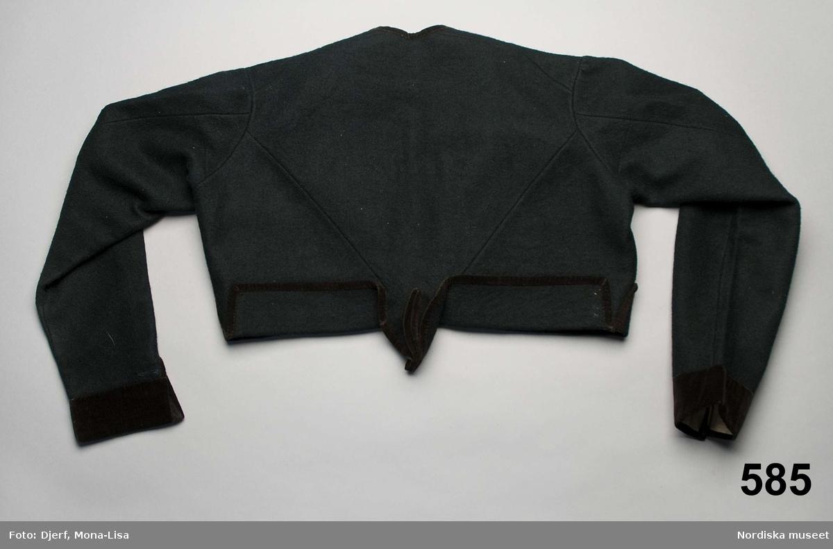Kvinnotröja av svart vadmal, 2 framstycken/sidstycken och ett ryggstycke med närmast trekantig form med spetsen nedåt  och avslutat i ett urstående skörtveck, hela nederkanten  uppvikt 6 cm och kantad med svart sammetsband, uppviket fastsytt i sitt läge. Vid halsringning kantad med sammet, rak framkant och på den högra överlappande kanten dubbla rader sammetsband. Isydd något svängd ärm med 2 sömmar och lätt rynkad på ärmkullen, 7 cm ärmsprund knäppt med en silverknapp och tränsat knapphål. Ärmen kantad med 5 cm svart sammet. Knäppning med 6 par hakar och hyskor av mässing, 2 mässingshakar bak vid skörtet att fästa mot kjolen. Fodrad med fin ljus linnelärft. Silverknapparna har otydlig stämpel.  /Berit Eldvik 2010-12-14