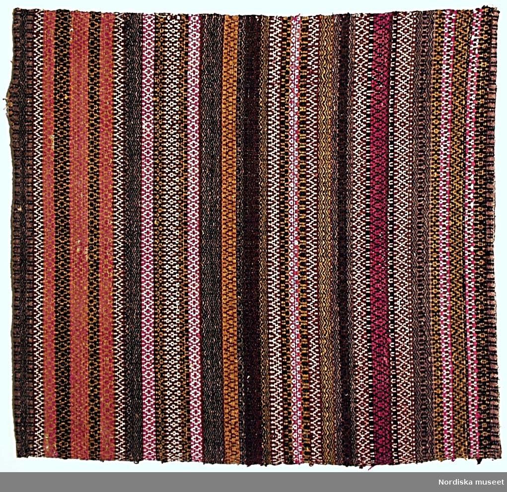 Täcke, del av. Varp: 2-trådigt S-tvinnat lingarn, 45 trådar/10 cm. Inslag: 1-trådigt Z-spunnet och 2-trådigt S-tvinnat ullgarn i flera färger samt vitt S-tvinnat bomullsgarn. Vävt i bunden rosengång på fyra skaft, helmönstrad i smala tvärgående bårder. Två stadkanter. Smal fåll i båda kortsidor. Den ena är sekundär. Täcken bestod vanligen av två hopsydda 60 - 70 cm breda våder. /Berit Eldvik 2002
