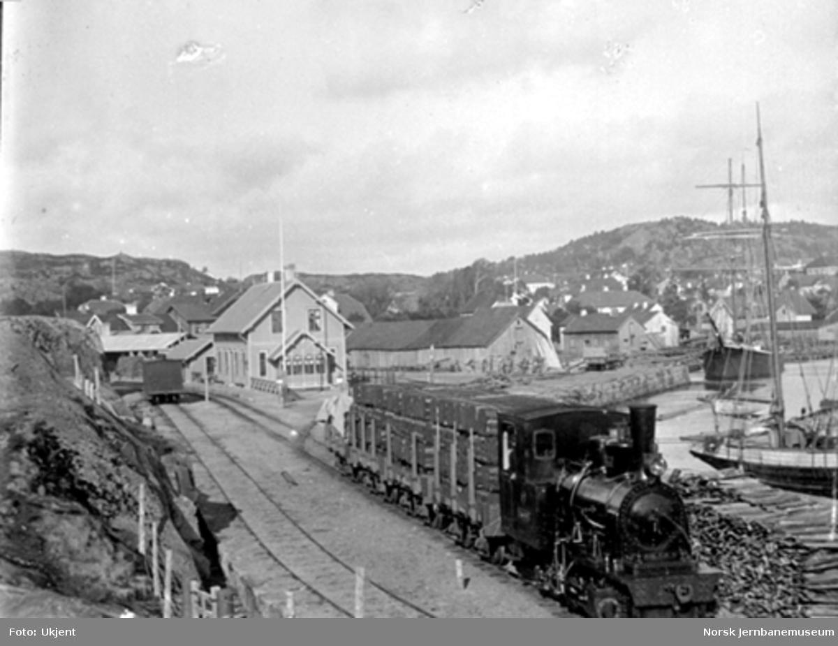 Damplokomotiv med godstog lastet med torvbunter på Lillesand stasjon