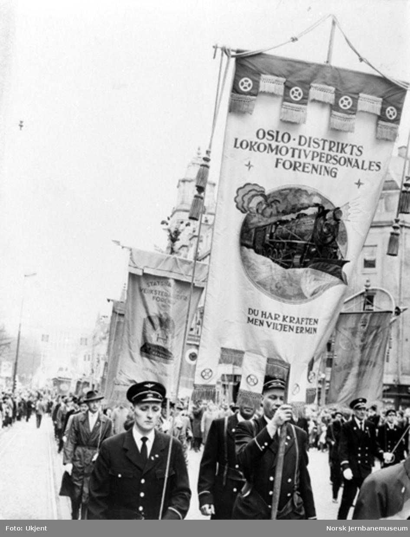 Representanter fra Oslo distrikts lokomotivpersonales forening i demonstrasjonstog med sin fane. Bak dem kommer Statsbanenes verkstedarbeiderforening, Oslo, med sin fane