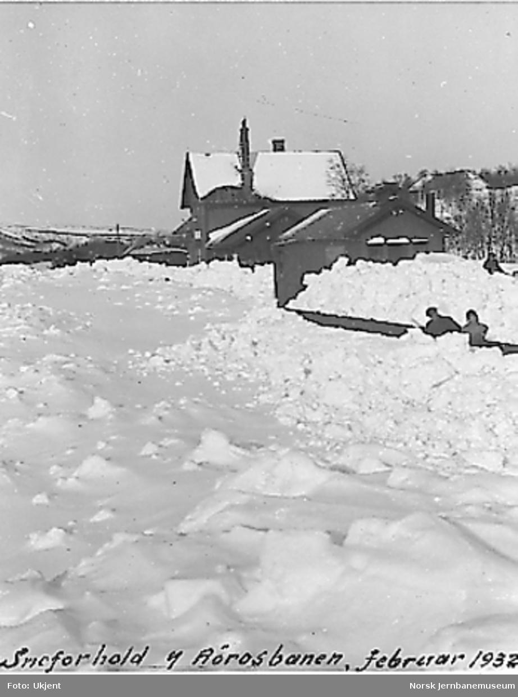 Snømåkere laster snø på godsvogner for bortkjøring fra Rugldalen stasjon. Utenfor stasjonsbygningen ser vi taket på en motorvogn av type 1