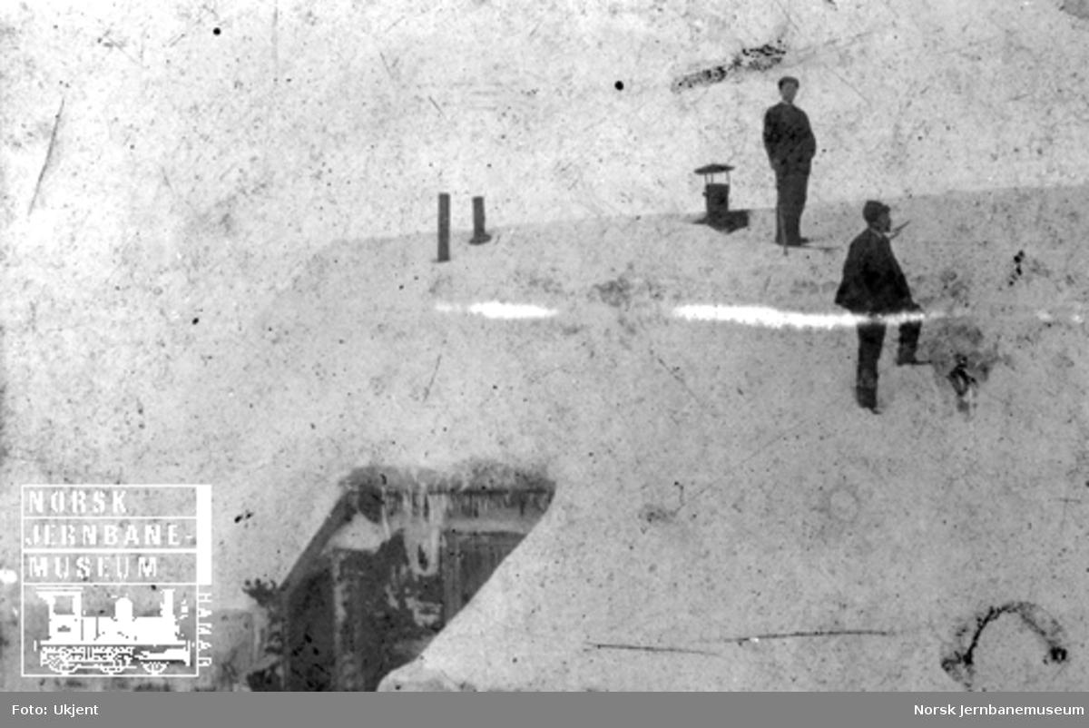 To mann på en snøfonn på taket på Hallingskeid handelsbod