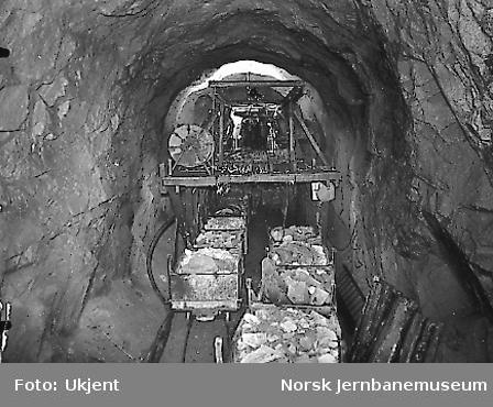 Bukk for framskaffing av trykkluft- og vannledning til boremaskiner m.v. i stuffen i Kvineshei tunnel, vestre innslag. I forgrunnen lastede vagger