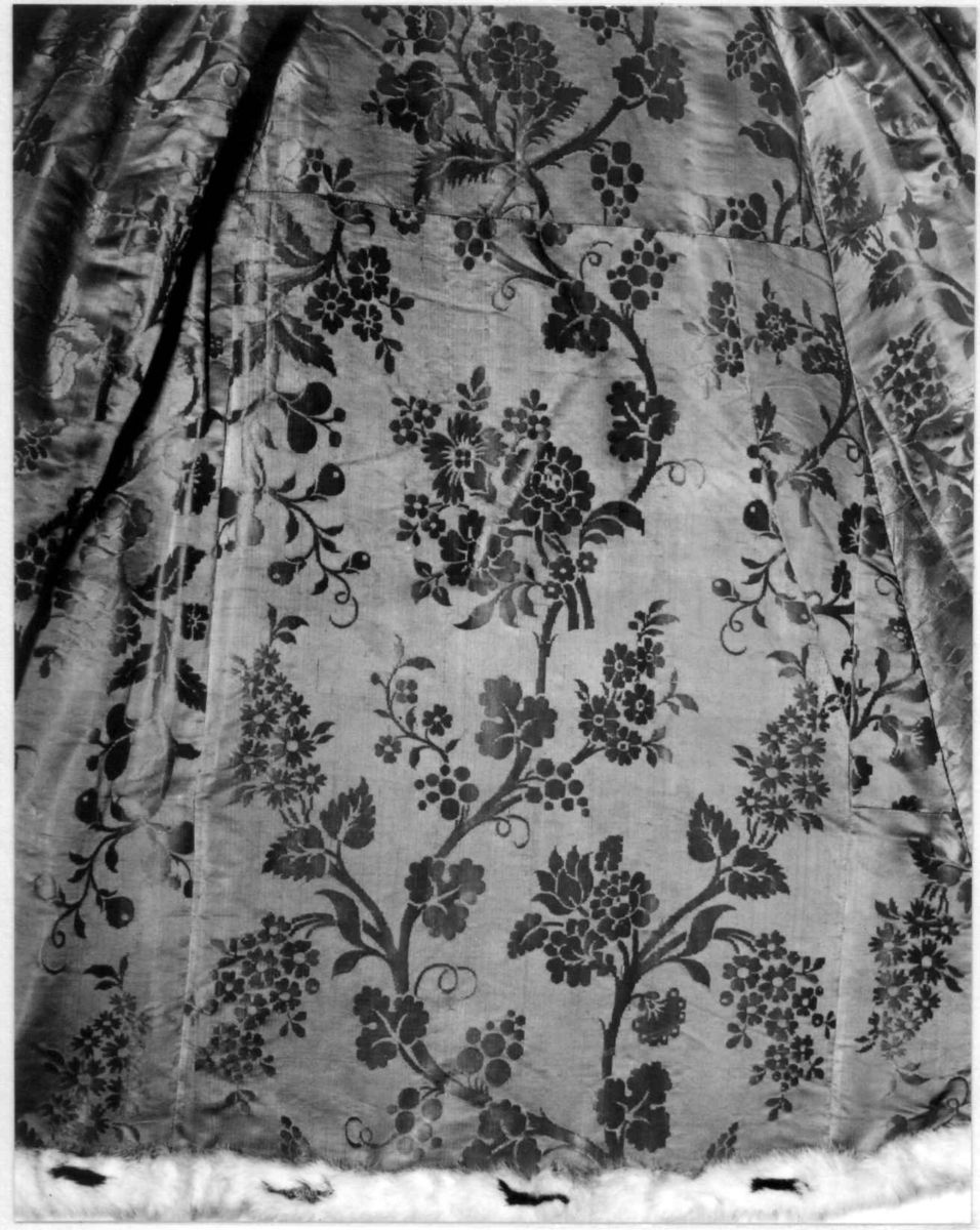 Cape av vattert silkedamask, foret med kattun med krappfargetrykk, kantet med imitert hermelin.