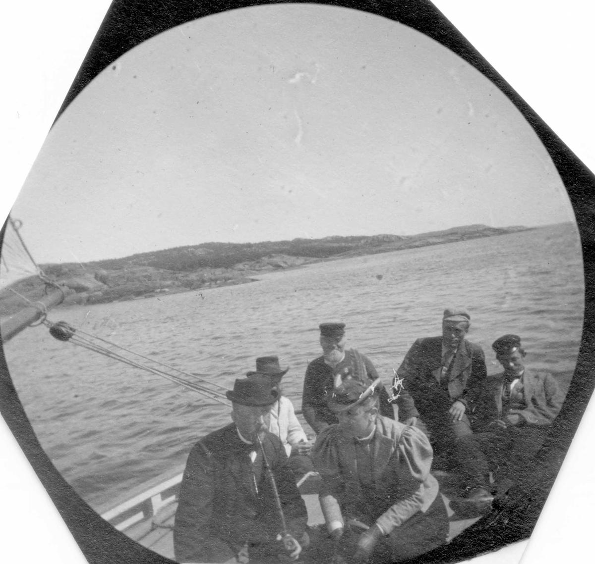 Fra botanisk ekskursjon med professor Blytt ved Ula, Tjølling, Vestfold. Mennesker ombord i seilbåt. Land i bakgrunnen.