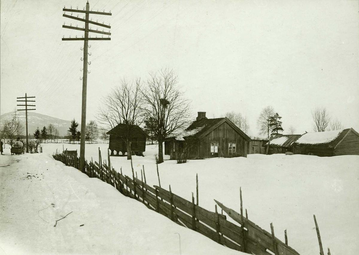 Plassen Vengerflaen, Eidsvoll, Øvre Romerike, Akershus. Husmannsplass sett fra vei om vinteren. Lysstolper og skigard langs veien.