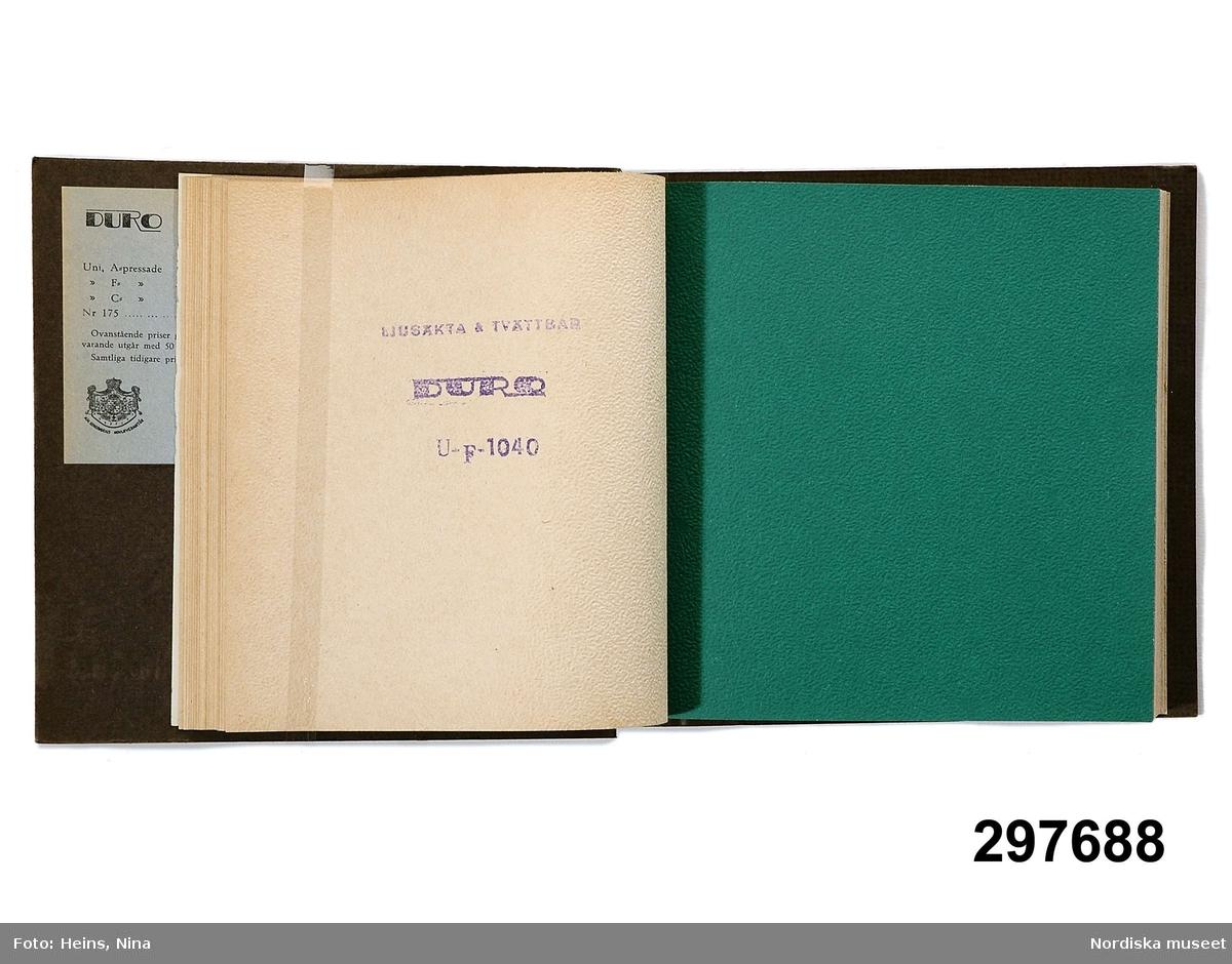 """Huvudliggaren: """"Tapetkarta, papperstapeter, enfärgade; grön pärm av pressad papp med i guld 'U 29/DURO/Ljusäkta tvättbara/AB Durotapet. Hagaström'; på insidan prislista daterad aug. 1952; proverna med pressad yta, imiterande väv; ljusa gråbeige färger, några i rött, gult, svart, grönt, blått m. m. Mått 20 x 22, 7 cm. Funnen i tjänsterum.""""  Katalogkort: """" Grön pärm av pressad papp, text med guld: 'U29/Duro/ 1 ljusäkta tvättbara/ A.B. Durotapet. Hagaström.' På insidan av pärmen prislista daterad aug 1952. Samtliga tapeter har pressad yta, i regel med fin grain eller imiterande väv. Övervägande ljusa gråbeiga färger, ett mindre antal i kraftiga färger: rött, gult, svart, mörkgrönt, mörkblått mm. EHk (=Elisabet Hidemark) /75. """"  Inget ytterligare att tillägga vid inventering 2007. /Cecilia Wallquist 2007-02-12."""