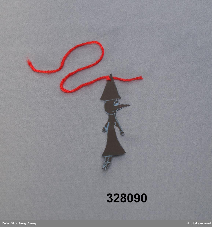"""Katalogkort: """"Pappershäxa tillverkad i pappersklipsteknik bestående av svart papp målad med blå krita. Upphänges med en tråd av rött garn. Har tillverkats av barnen på Fritidshemmet Skattkammaren i samband med halloweenfirande hösten 2001. Ingår i Antikvariska avdelningens hallweendokumentation 2002 bestående av foton, intervjuer och deltagande observation. Lena Kättström Höök, Anna Asplund dec 2002."""""""