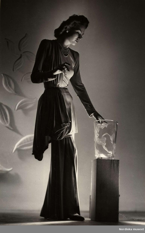 Franska avdelningen på Nordiska Kompaniet 1944. Kvinnlig modell poserar i dramatisk ljussättning iförd draperad aftonklänning. På ett podium intill henne en glasvas och på väggen bakom ett arrangemang med blad.