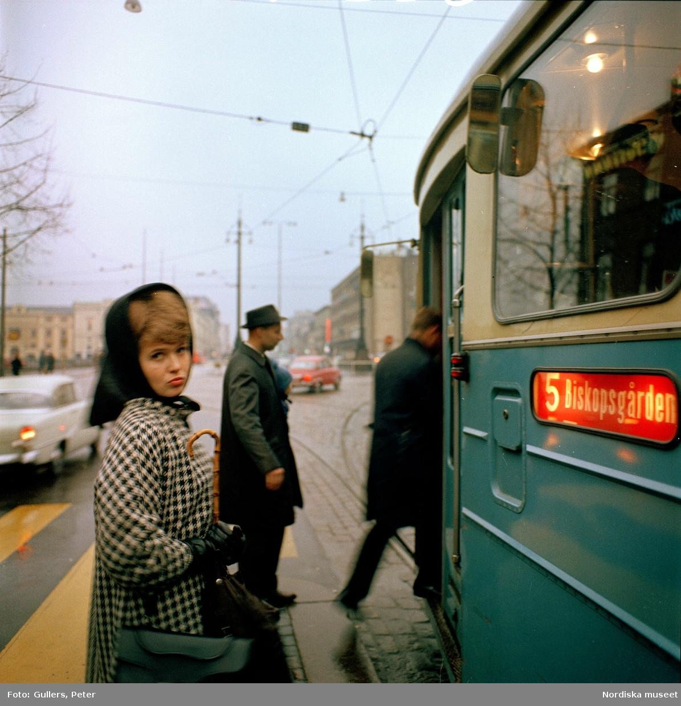 Göteborg. Kvinna invid spårvagn. Två män stiger på.