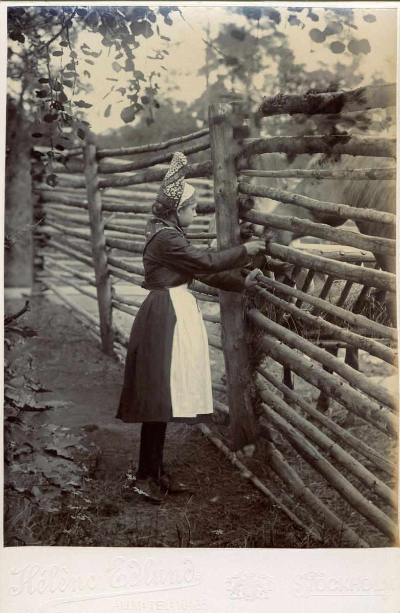 En flicka iklädd folkdräkt står framför en hästhage.