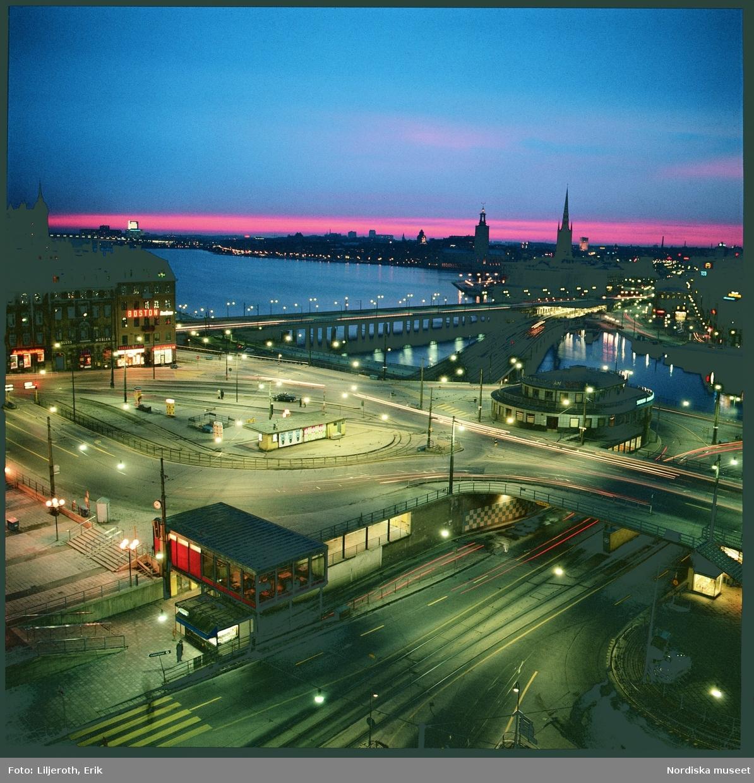 Slussen, Stockholm. Stadsbild med vy över Slussen, i bakgrunden Riddarholmen med kyrkan och Kungsholmen med Stadshuset i förgrunden. Det är kväll, mörkret har sänkt sig och gatubelysningen tänts, men himlen i väster är fortfrarande orange och rosa efter solnedgången.
