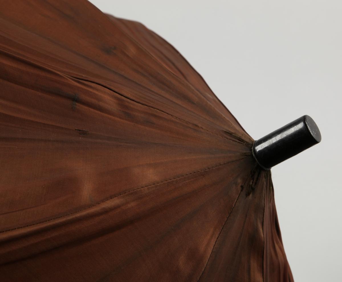 Ringformet håndtak av elfenben. Dusk av skinnstrimler i benperle, festet til treskaftet med skinnrem. Metallspiler.