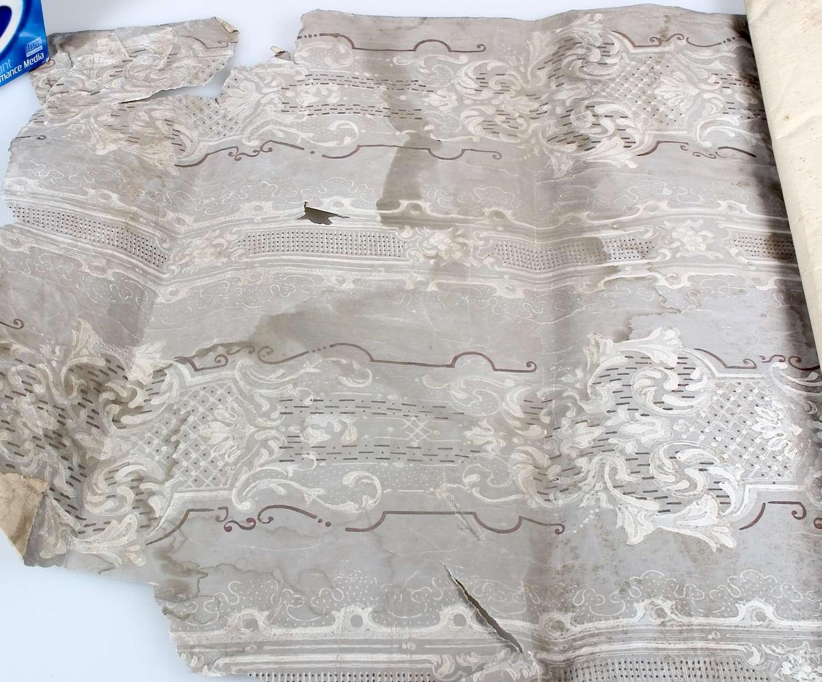 En tapetrulle, tapet av papper, tryckt mönster i vitt och brunt på grå botten.