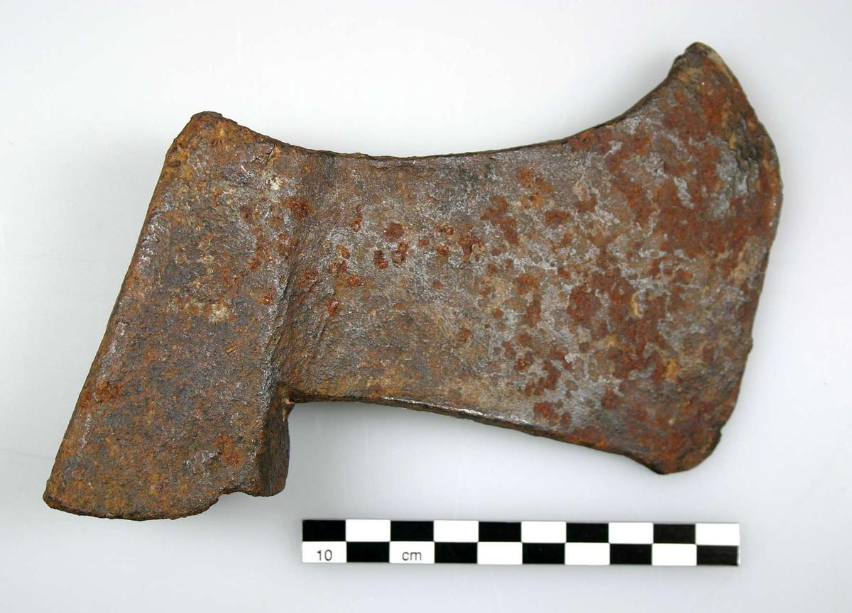 Yxa med utdraget fronthörn. Rak undersida, längd 9,0 cm. Ränna i skafthålet, delar av översidan i två delar, cirka 2,5 cm.