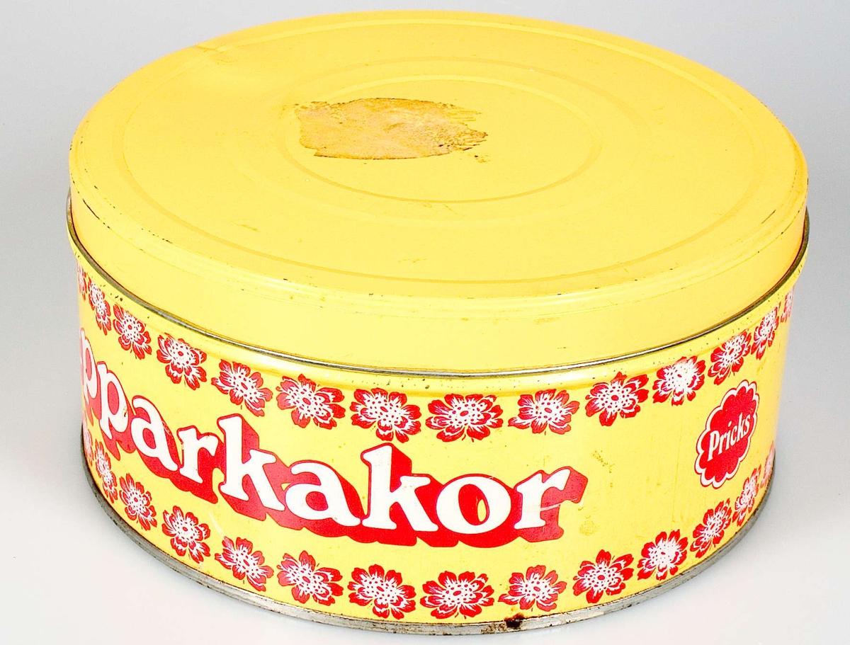 Pepparkaksförpackning av järnplåt. Tryckt dekor: blommor i rött och vitt på gul botten. Gult lock. Text i rött och vitt: Pepparkakor. Logotypen Pricks i rött och vitt.