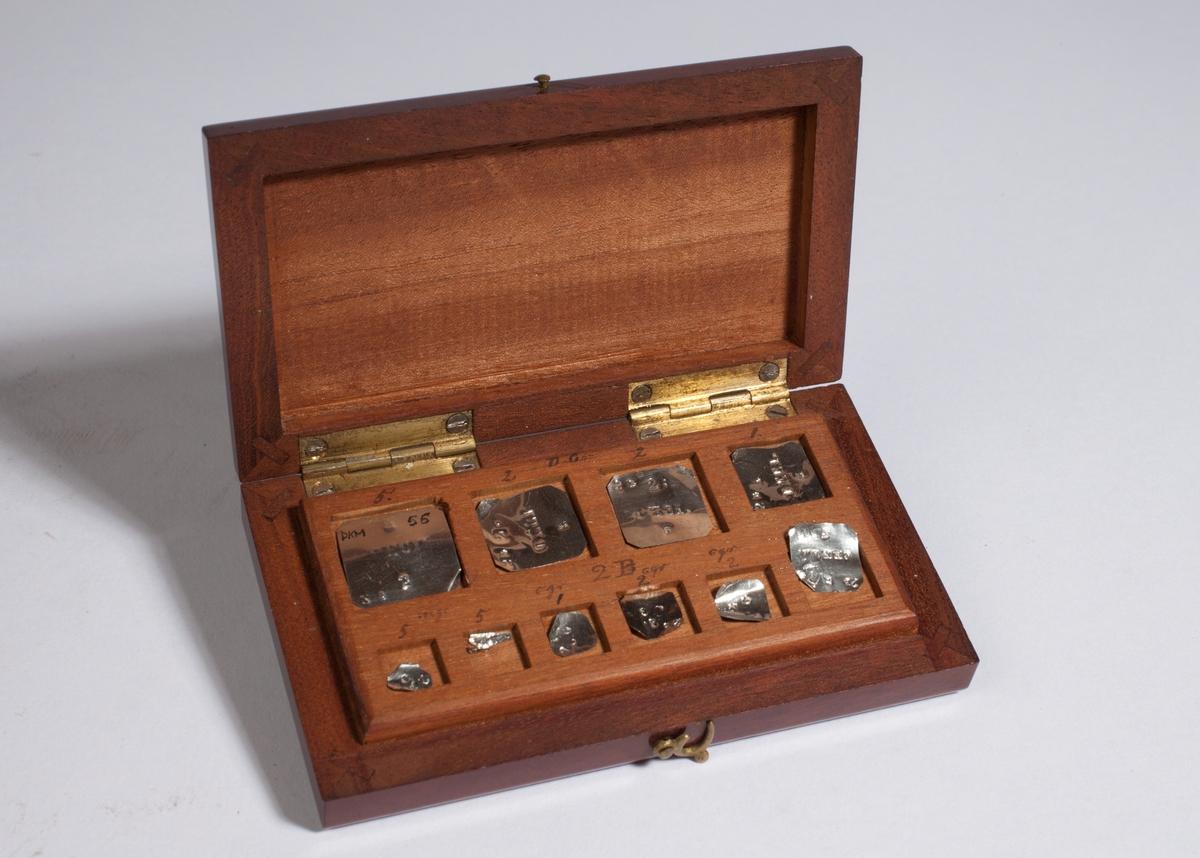 Rektangulær kasse med ti lodd.