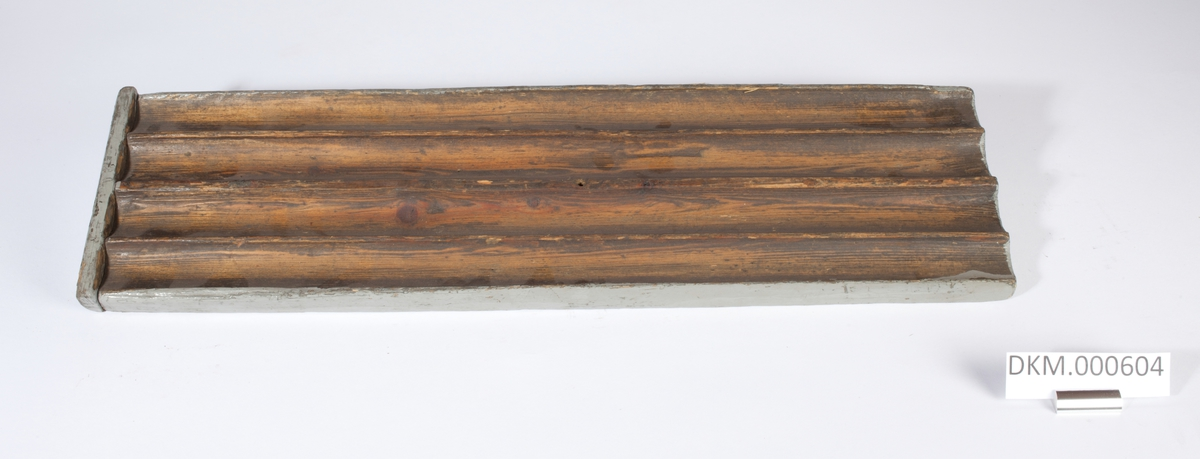 Avlang planke med fire langsgående riller som er åpne i den ene enden og stengt av plankens ytterkant i den andre enden. Planken er gråmalt i kantene.