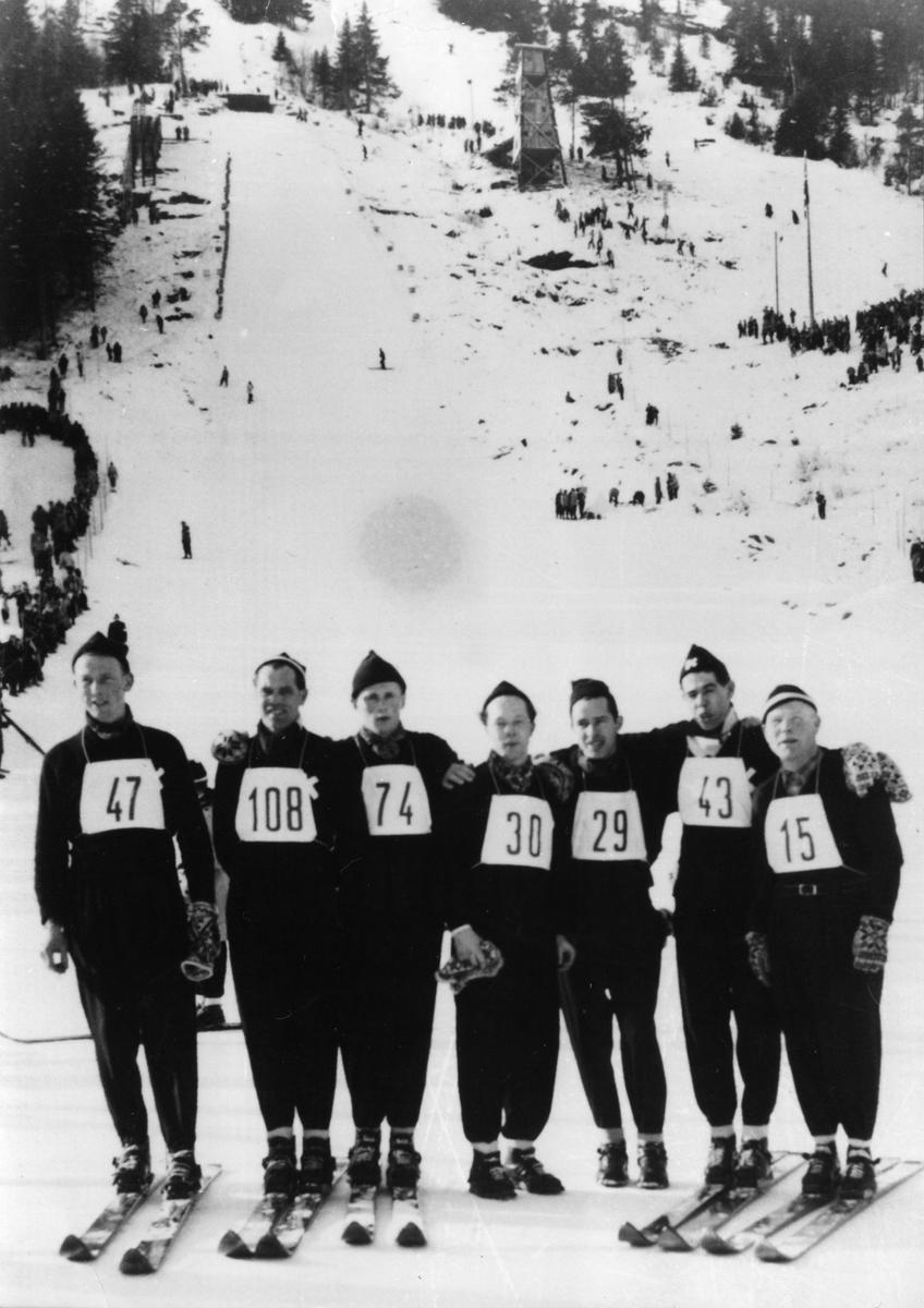 Kongsberghoppere under NM i Barvallen, Voss: John Kongsgård, Arne Ulland, Kåre Fulsebakke, Svein Lien, Ivar Nilsen, Ernst Knutsen, Arnholdt Kongsgård. Skijumpers form Kongsberg during the National Championship at Voss 1953.
