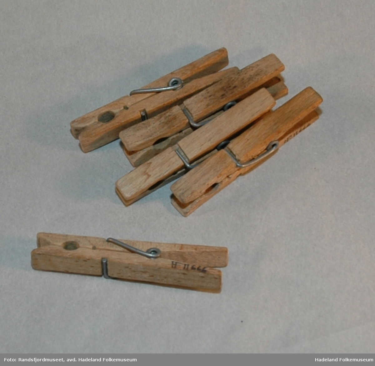 Av to freste trestykker (løvtre), holdt sammen av stålfjør. Masseprodusert.