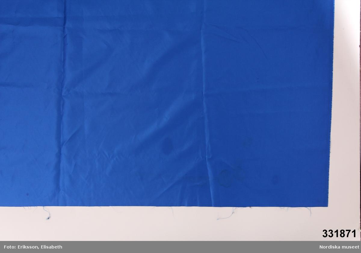 Tygstycke, vävt, blått, omönstrat, ofållat. Konstfiber? /Cecilia Hammarlund-Larsson 2013-07-01