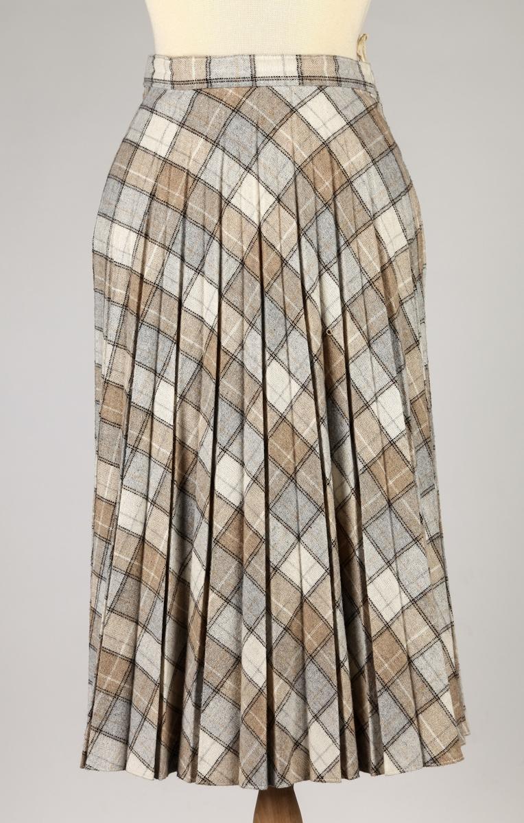 Solplissert skjørt, halvt rundklipt, glidelås, linning. Knfeksjon Pinetta-mod.510. Made in Denmark. Rutet.