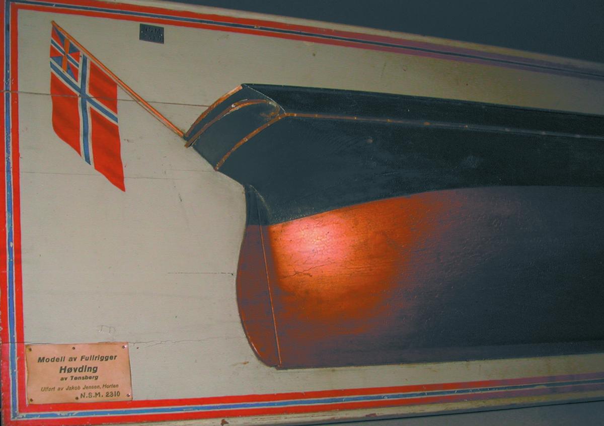 Halvmodell av fullrigger 'Høvding' (HKRV) av Tønsberg. Sort med gullstripe, brun bunn, lyslakkert dekk, montert på hvit plate med ramme i norske farger. Norsk unionsflagg med 'sildesalaten' malt akter.