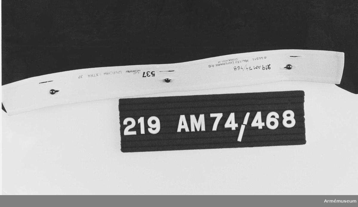 Vit enkel krage av linne, hårdstärkt. Storlek 37. Försedd med sex knapphål för fastsättning i attila m/1873. Märkt på insidan.