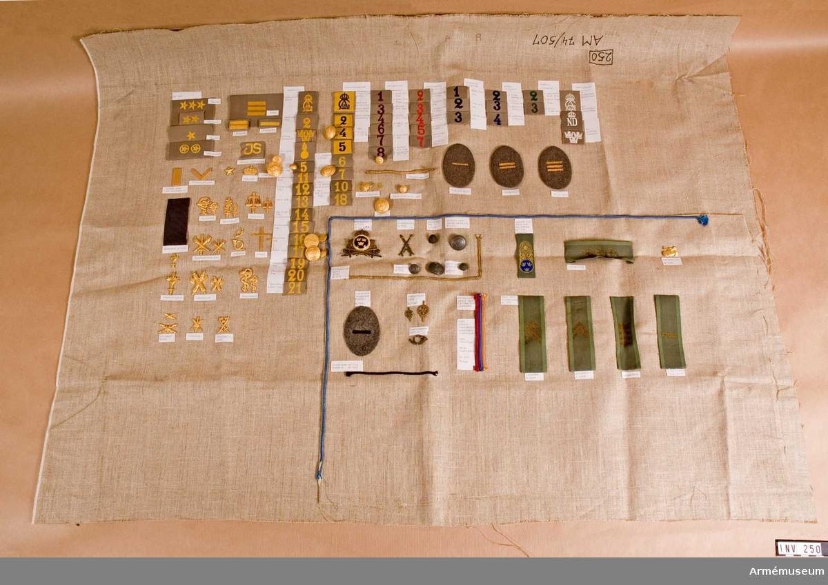 Div. förbandstecken för general. På oblekt linne är uppsytt diverse förbandstecken, mössmärken, agraff general, mössband, tjänstetecken, knappar m m. Visande den gåva från MI 451 i Filipstad som museet har fått. Resten är utsorterat i askar för respektive årsmodeller.