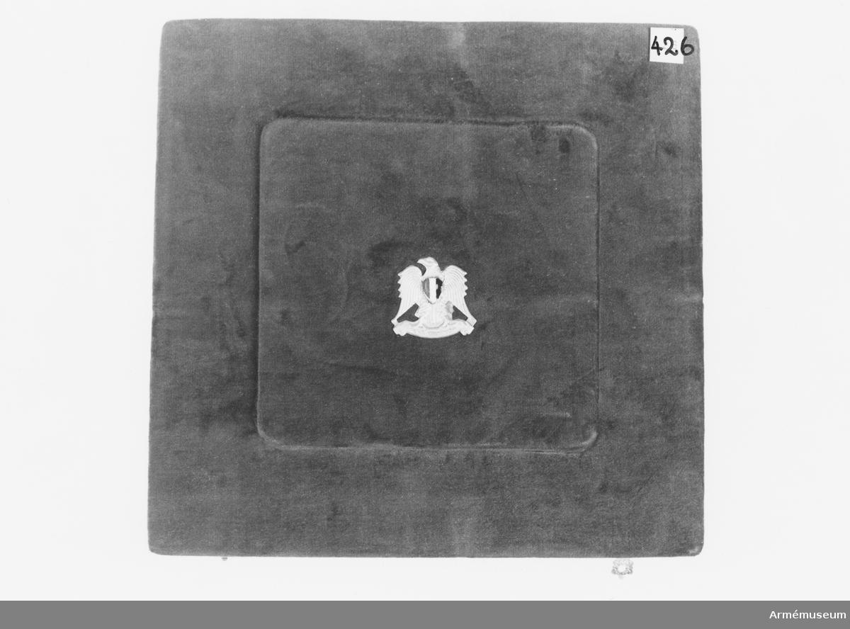 Samhörande nr är 294-299, 321-350, 400-448 (425-426). Fodral t sköld från 2. egyptiska armén (Kanthara). Mörkrött sammetsfodral. Mottagen vid besök i smb med inspektion av svenska UNEF-kontingenten nov 1974. Det yttre helt klätt i sammet. På mitten av locket den egyptiska örnen med en emaljerad bröstplåt i rött, vitt och svart. Spännen av gulmetall. Insidans botten klädd med veckad sammet. Fördjupning för skölden. Dekorationssnodd av silke och silversnodd. Lockets insida är klätt med vitt konstsiden. Spärrar av vitt konstsidenband.