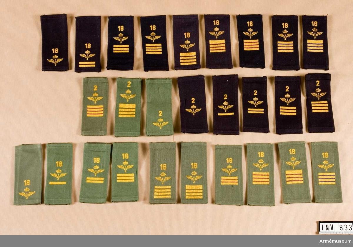 Axelhylsor m/1951, Södertörnskolor. I två lådor. Innehåll: ca 3 000 axelhylsor, 1 000 ärmmattor (på rullar). Blå =m/51. Grön= - . Rustmästare: fyra streck varav ett tjockt, 100 blå, 200 gröna. Överfurir: fyra jämntjocka streck, 200 st blå, 100 st gröna. Korpral: tre jämntjocka streck, 200 st blå, 100 st gröna. Vice korpral: ett streck, 250 st blå, 100 st gröna. Menig: inget streck, 150 s blå, 200 st gröna. RUSTMÄSTARE- trafikpersonal: se ovan+ljusblått kläde, 100 st blå; teknisk personal: se ovan+violett kläde, 100 st blå, 100 grön. ÖVERFURIR- trafikpersonal: se ovan+ljusblått kläde, 100 st blå, 100 grön; teknisk personal: se ovan+violett kläde, 100 st blå, 100 grön. FURIR- teknisk personal: se ovan+violett kläde, 200 st grön. Ärmmattor för värnpliktiga, furir, furir-tekniker, överfurir, överfurir-tekniker, överfurir-trafik, rustmästare, vardera om 100 st. Flottiljsiffror m/30, 10 mm och 18 mm höga, vardera om 100 st.