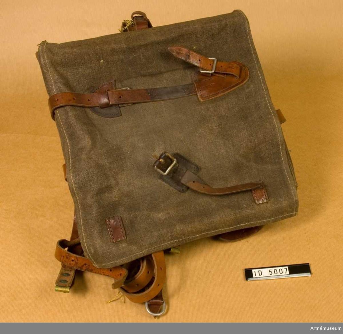"""Ränsel m/1898?. Av gråbrun smärting (eller kanfas), fodrad med grått linne. Remmar av brunt läder. Trästyvnad på insidan upp- och nedtill. Av fodertyget ett extra fack i locket. Locket märkt """"A.I.F. 1922""""."""