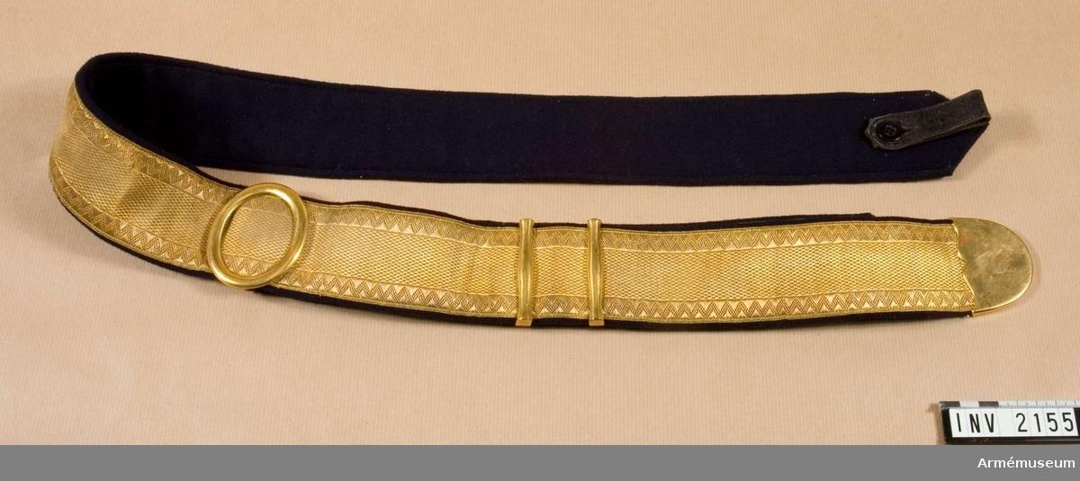 Av 50 mm bred guldgalon med förgyllda beslag. Fodrad med mörkblått kläde och med släta, förgyllda beslag. Remmen fästes med knappar vid kartuschlådan med ändarna korsvis över dess baksida. Nyttjas till paraddräkt av officerare och vederlikar.  Källa: Arméns rulla 1908, sida 278.