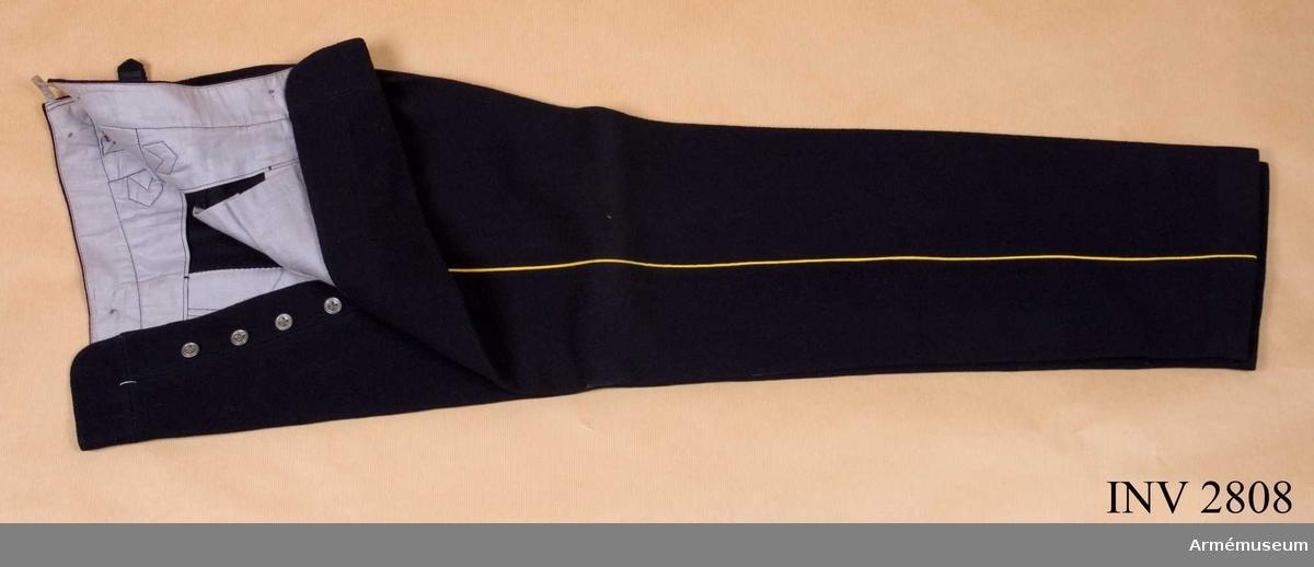 """Stl B 52. Av mörkblå kommisskläde med gul passpoal längs med  yttersömmen. Kompositionsknappar i livet för hängsle. Livet är  skott med grått bomullstyg på vilket det finns två stämplar:  """"183 I F"""" och krona """"I 9 1926"""". Fickor i var sidsöm samt tampar  bak för att reglera livvidden."""