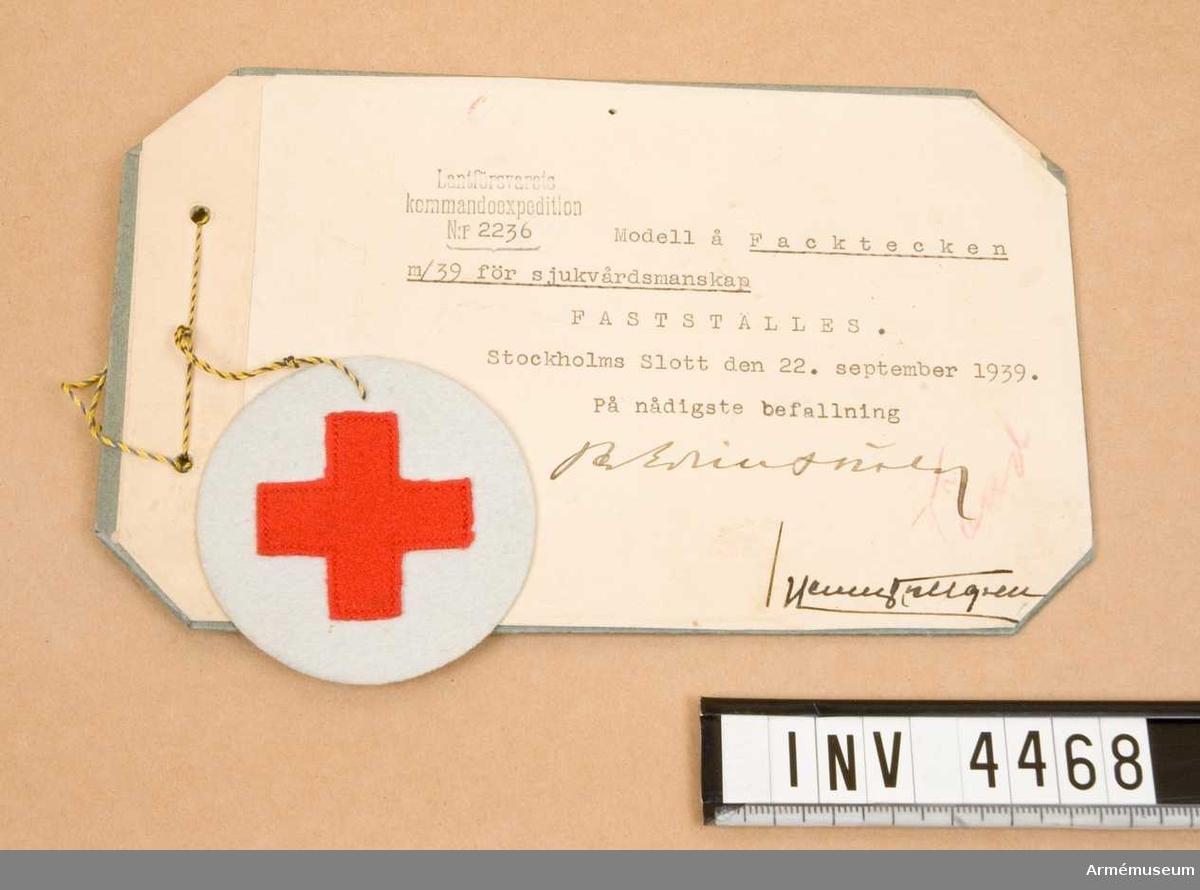 """Tecken m/1939, fack-, sjukvårdsmanskap.Utgöres av ett kors, 36x36 mm, av rött kläde fastsytt på ett cirkelrunt underlag av ylletyg, d 60 mm. Detta tj.tecken var i bruk lånt tidigare f sjukvårdsutbildad personal, men kom att inrangeras bland övriga facktecken m/39 som fastställdes nämnda datum. Anbringades på H ärm på vapenrock/kappa, 120 mm ovanför ärmens underkant. För off/uoff tillv. märket i metall, lackerat eller emalj och anlades på bägge ärmarna. Från år 1953 tillv. det uteslutande av metall och benämndes facktecken m/1953, Fr o m införandet av uniform m/1958 slopades anläggandet av facktecken. Vidhängande etikett anger fastställelsedag: """"Stockholms Slott den 22.sept. 1939 Per Edvin Sköld /Henry Kellgren""""."""