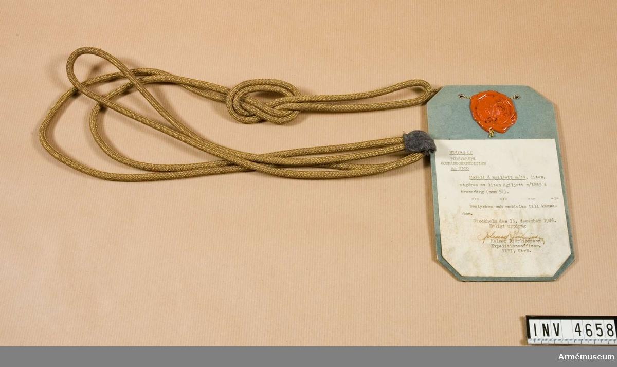 """Fastställdes år 1816 under benämning """"liten ägiljett m/1889"""". Tillv. i guld-/silverfärg. Vid införandet av uniform m/39 fastställdes att alla tjänstetecken skulle vara i bronsfärg och ägiljetten kom därför att få samma utförande och benämning """"liten ägiljett m/39"""" fastställdes. Tillv. av bronsfärgad gulddragartråd, innehållande  5 gr guld per kilo metall. Utgöres av två tränsar i olika längd. Dessa är i ena änden fästade vid en bit tyg som på lämpligt sätt kan fästas på axel under axelklaff. Var träns består av tre snören, ca 5 m tjocka. De båda yttre utgöres av en länk vars fria ändar är fästade vid nämnda tyg. Det mittersta snöret är grovt flätat. Den längre tränsen har en valknut. Bars endast t uniform m/39. Vidhängande etikett anger fastställelsedag: """"Stockholm Slott den 4.april 1941 Per Edvin Sköld Henry Kellgren"""".Bärandeföreskrifter enl UniA 1962 års utgåva: Bärs t daglig dräkt av vakthavande adjutant hos H M Konungen, H K H Kronprinsen och de kungliga prinsarna samt t samtliga uniformsdräkter av adjutant hos statsråd, överbefälhavaren och chefen f armén. Liten ägiljett anbringas på vapenrock längst ut på H axel under axelklaff. Tränsen fästs på den översta knappen i vapenrocken. Då det av praktiska skäl befinns erforderligt, får liten ägiljett på motsvarande sätt bäras även t ytterplagg. Då adjutant hos statsråd, överbefälhavaren och chefen f armén tillika är adjutant vid kunglig stab (motsvarande), överadjutant, stabsadjutant eller teknisk stabsofficr, anläggs dock stor ägiljett t högtidsdräkt."""