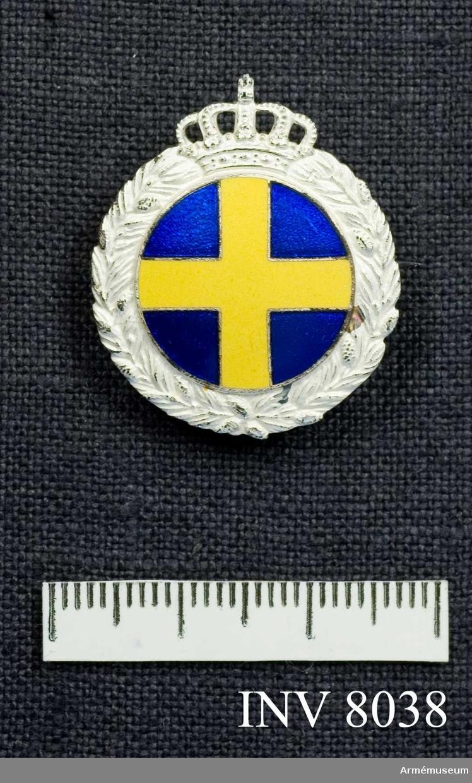 Samhörande gåva 8020-. Märke med i mitten ett gult kors på blå botten, det hela i emalj. Krans i silver. Tillverkare Sporrong. Färg silver, blå och gul emalj.
