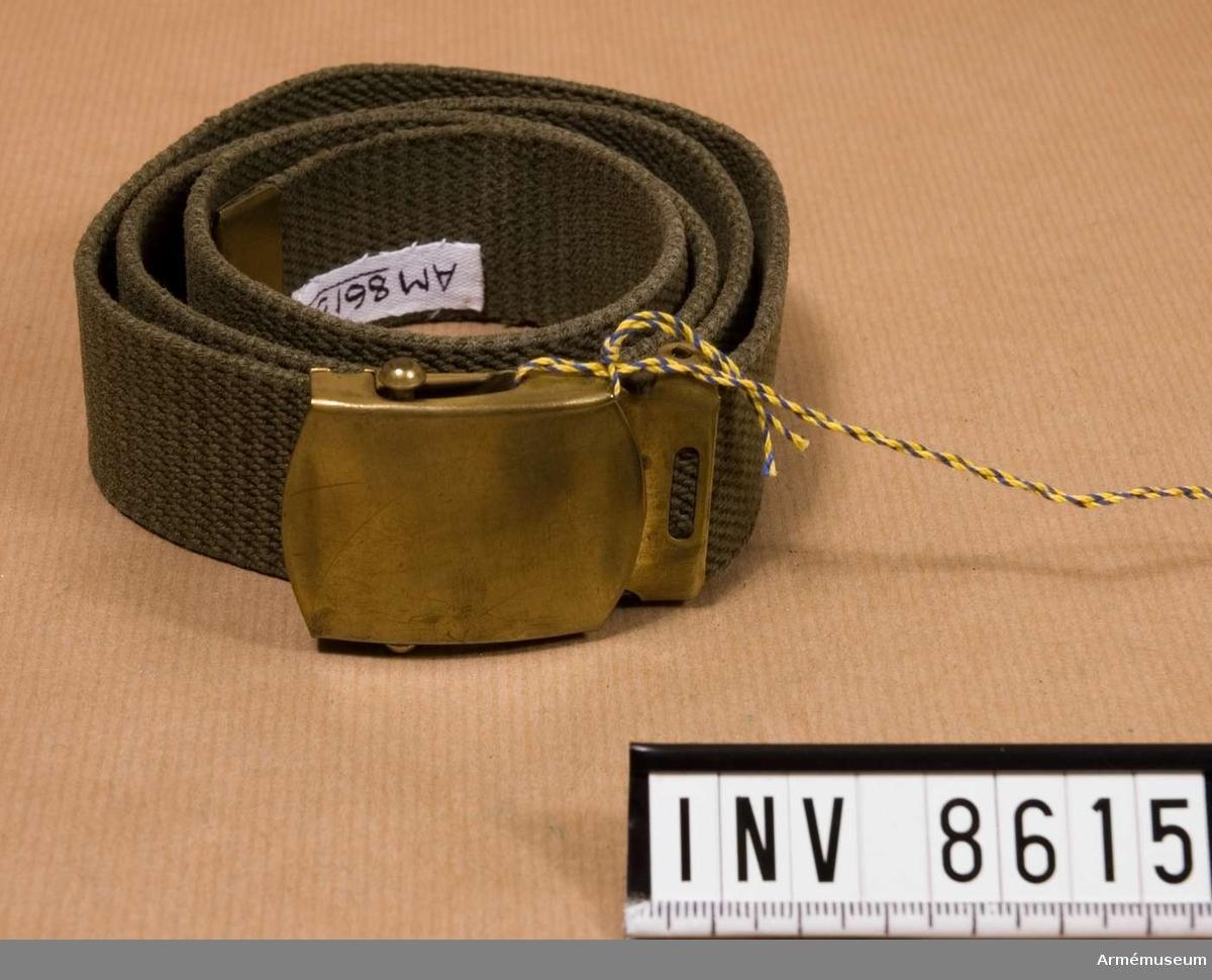 Byxbälte m/1968, ljusgrön, grbrgr. Tillverkad av gråbrungrönt textilband med spänne av mässing. Källa Uni A 1977 6:16 d.