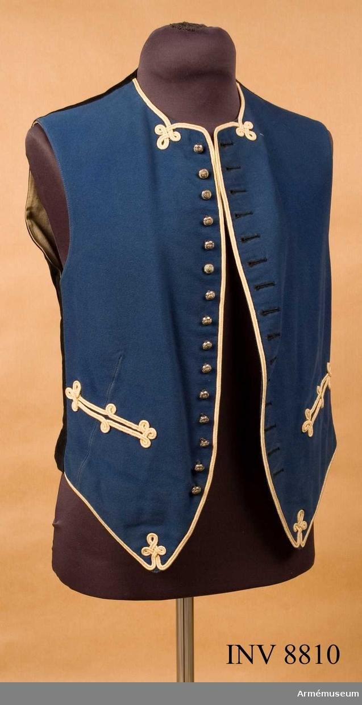 En kort väst sydd i blått kläde garnerad med vita  redgarnssnören runt framstyckena och runt fickorna. Höger framsycke försett med 15 små knappar av trängens modell 1891. Motsvarande knapphål på  vänster sida är handsydda med svart knapphålssikte. Denna typ av väst använde kaddetterna som mässväst  på Karlberg/ det regemente de tillhörde, eller  fantasiutförde.