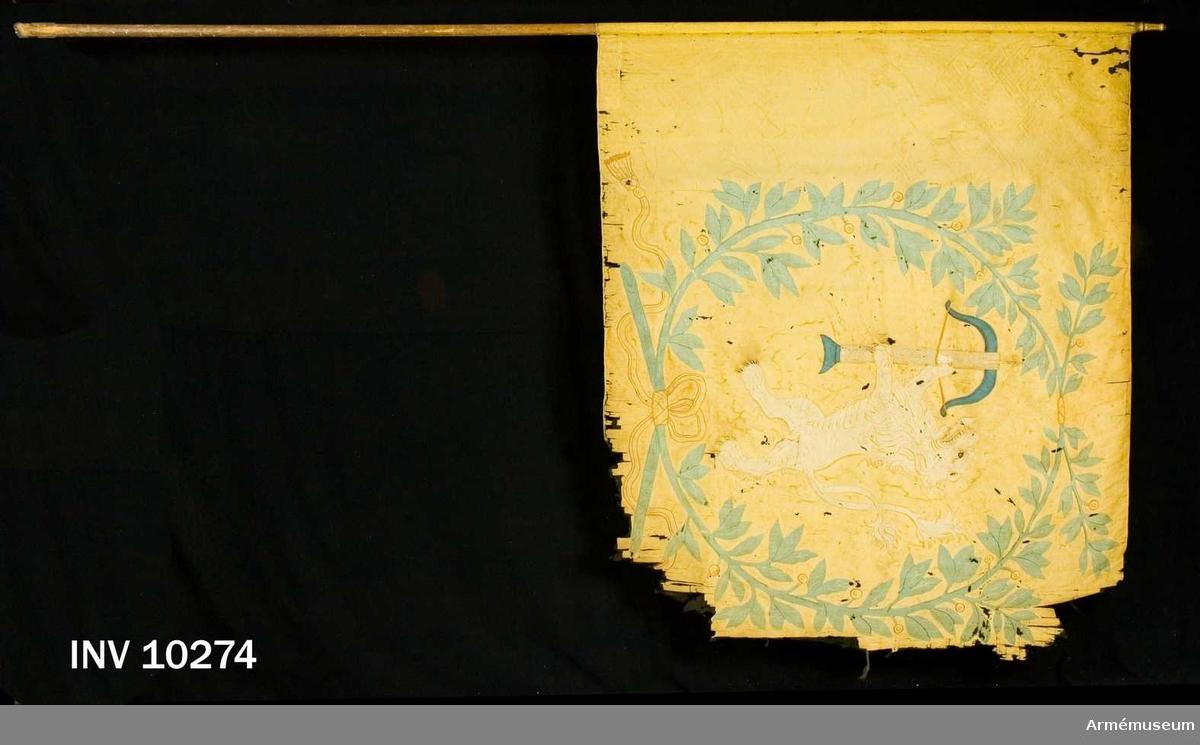 Grupp B I.  Fanduk av gul taft med insydda emblem (intarsia): Smålands sköldemärke, ett dubbelsvansat, rött lejon förande ett spänt  armborst i vitt med blå båge och kolv samt pålagd pil, allt omgivet av lagerkrans i grönt av två nedtill med bandrosett hopknutna lagerkvistar med rikt bladverk och röda bär. Bandet gult med bruna, broderade konturer, avslutat i tofsar. Fastspikad på stången med kupiga mässingsstift och sidenband. Stång av brunpatinerad furu, 3,50 m lång. Spets av förgylld mässing.  Tillverkad 1717 av Johan Wijkman.