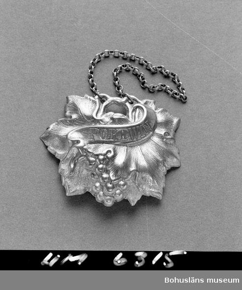 """Flaskkylt i nyrokoko med graverad text """"Portvin"""" på ett språkband. Rik dekor av vindruvor och vinlöv. Identisk med UM 6314 förutom texten. Framsidans silverskikt starkt slitet, delvis helt borta Försedd med nysilverkedja ( ej med i angivna mått) för att kunna hängas kring karaff- eller buteljhals  Ur handskrivna katalogen 1957-1958: Flaskskylt i silver I form av 2 vinlöv med klase. 6,7 x 5,5 cm Bandaroll med """"PORTWIN"""" Hänger i en liten kedja Hel  Lappkatalog: 57"""